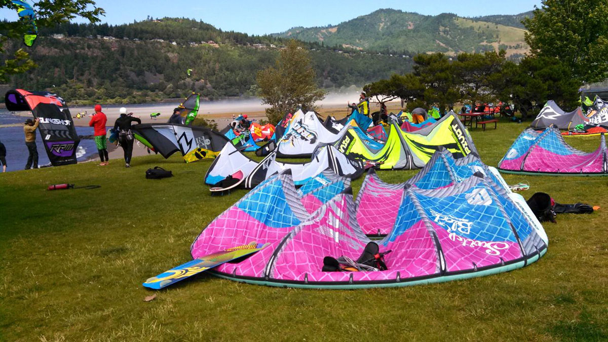 The bright neon colors of sails pop against the deep greens, blues and browns of the Columbia River Gorge.