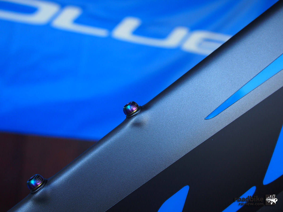 Anodized titanium water bottle cage bolts are customized with Blue's logo.